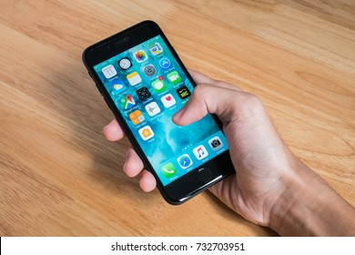 Bangkok, Thailand - October 11, 2017 : Apple iPhone 7 held in one hand showing its screen with Home Screen.