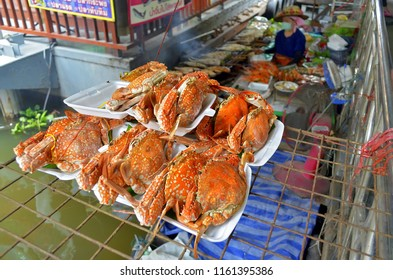 Bangkok, Thailand - October 12, 2014: Big orange crabs sold on a bark at Taling Chan Floating Market with the vendor in the blurred background.