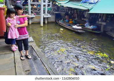 Bangkok, Thailand - October 12, 2014: Thai little girl with her mother feeding fish in the klong at Taling Chan Floating Market.