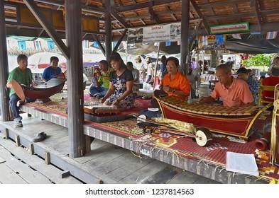 Bangkok, Thailand - October 12, 2014: Thai people playing traditional musical instruments at Taling Chan Floating Market.