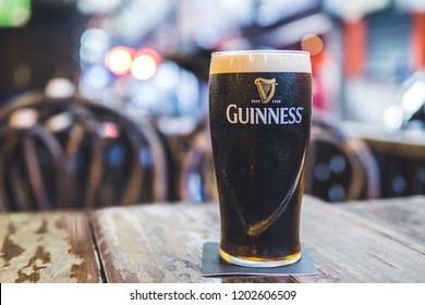 BANGKOK, THAILAND - OCTOBER 12, 2018: A pint of Guinness stout on the table with blurry background.