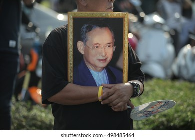 Bangkok, Thailand- October 14, 2016: A man hold the portrait of King Bhumibol Adulyadej during a convoy carrying the body of the King from Siriraj Hospital to the Royal Palace.