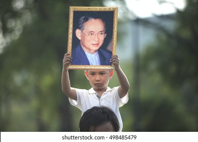 Bangkok, Thailand- October 14, 2016: A boy hold the portrait of King Bhumibol Adulyadej during a convoy carrying the body of the King from Siriraj Hospital to the Royal Palace.