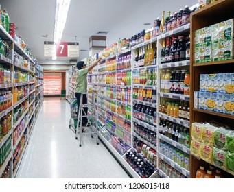 BANGKOK, THAILAND - OCTOBER 14: Unidentified supermarket employee organizes and stocks aisle 7 in Foodland Supermarket in Bangkok on October 14, 2018.