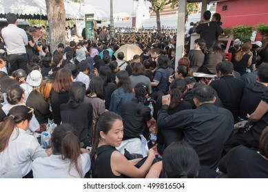 BANGKOK, THAILAND - OCTOBER 14,2016 : Mourners sit on the ground to bid farewell to His Majesty, whose body was transported in the motorcade from Siriraj Hospital to the Grand Palace