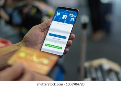 BANGKOK, THAILAND - October 15, 2017: Facebook signup web page app on smart phone with user sign in registration screen using social networking and credit card in another hand