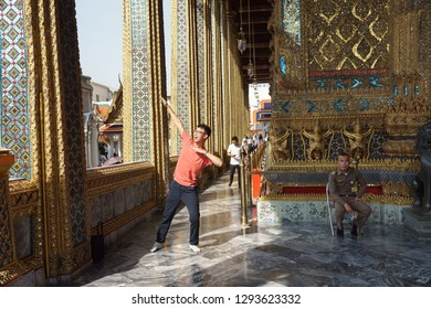 Bangkok, Thailand - October 15, 2018: Chinese tourists acts a superhero pose for taking a photo in the temple of Emerald Buddha, Wat Phra Kaew, Bangkok