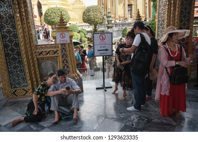 Bangkok, Thailand - October 15, 2018: A couple of tourists review the images on smartphone on the temple of Emerald Buddha's floor at Wat Phra Kaew, Bangkok