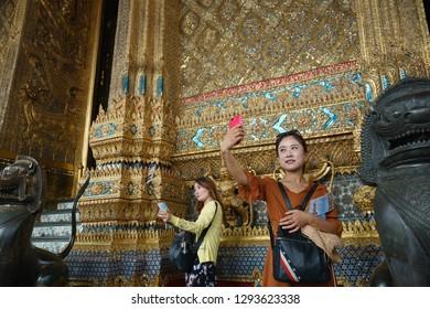 Bangkok, Thailand - October 15, 2018: Chinese tourists taking selfie photo with smartphone at Wat Phra Kaew, Bangkok