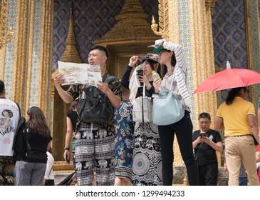 Bangkok, Thailand - October 15, 2018: Chinese tourists visit Wat Phra Kaew by using a tourist brochure, Grand Palace, Bangkok