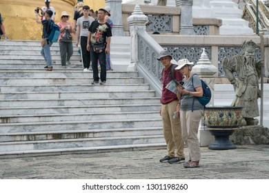 Bangkok, Thailand - October 15, 2018: Tourists visit Wat Phra Kaew by using a tourist brochure, Grand Palace, Bangkok