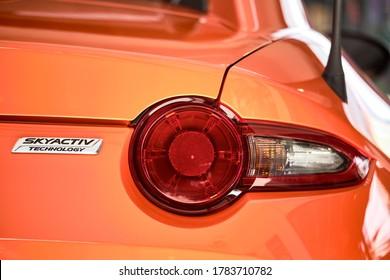 BANGKOK, THAILAND - OCTOBER 16, 2019: Rear taillight of Mazda MX5 with reflection on orange paint. Luxury sports car after paint polishing & ceramic coat. Car detailing & paint protection background