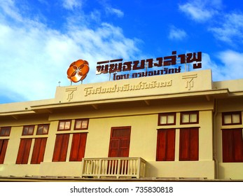 BANGKOK, THAILAND - OCTOBER 17, 2017: Pipit Banglamphu museum front sign in red Thai text language, with flower shiny metal logo, on yellow painted antique traditional style building, wooden windows