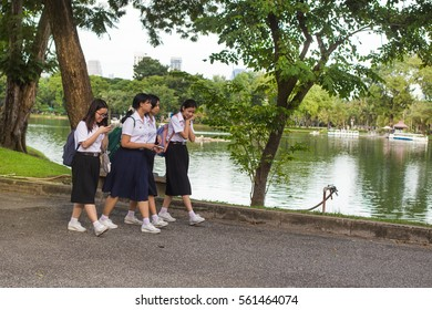 Bangkok, Thailand - October 20, 2016. Local school girls walking in Lumphini park after school wearing uniform.