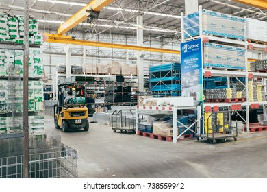 BANGKOK, THAILAND - OCTOBER 20, 2017: Storehouse full of construction equipments and materials with male employee driving folklift is on duty.