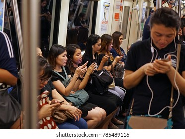 Bangkok Thailand - October 20, 2017: The passengers waiting and using smartphones to kill time inside MRT subway train, Mobile phone addiction lifestyle daily, Social technology telecommunication