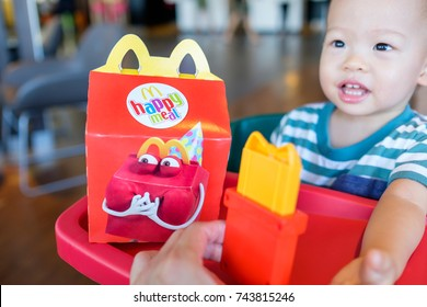 Bangkok, THAILAND - October 21, 2017: Cute little Asian toddler boy sitting in high chair eating happy meal & playing toy with dad at McDonald's restaurant, Selective focus at Happy meal packaging