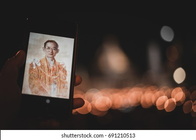 Bangkok, Thailand- October 22, 2016: Hand holding the portrait of King Bhumibol Adulyadej on mobile phone to pay respects outside The Grand Palace in Bangkok, Thailand, October 22, 2016.