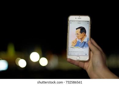 Bangkok, Thailand - October 22, 2016: Thai people show King Bhumibol Adulyadej photo on mobibe phone outside The Grand Palace.