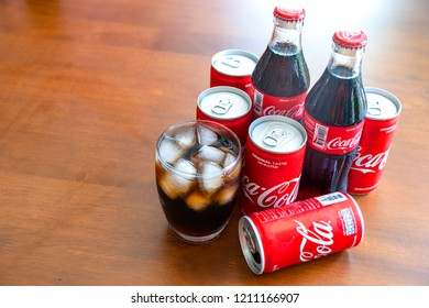 BANGKOK, THAILAND - OCTOBER 23, 2018: Coca-Cola with ice in glass and can,bottle on wooden background.. Coca-Cola is a carbonated soft drink sold in stores and restaurants