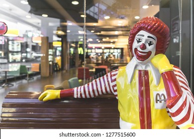 BANGKOK, THAILAND - October 23, 2018 : Portrait of Ronald-Mcdonald sitting on bench in front of McDonald's restaurant. ., People buying fast-food from McDonald's Restaurant