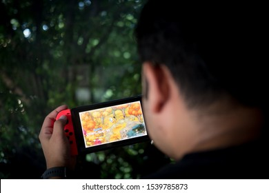 Bangkok, Thailand - October 24, 2019. Man playing game of Doraemon Story of Seasons in Nintendo Switch. The game combines the farming simulation elements from the Story of Seasons series and Doraemon