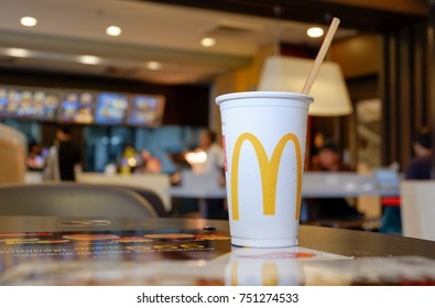 Bangkok, Thailand - October 26, 2017 : Cup of McDonald's Cola with Straw in the background of the McDonald's restaurant. McDonald's Corporation is the world's largest fast food restaurants.