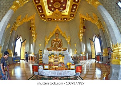 Bangkok, Thailand, October 28, 2014 - Wide angle interior view of the Wat Traimit with visitors and a front view of the solid gold Buddha statue.