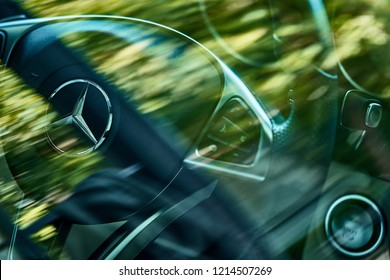 BANGKOK, THAILAND - OCTOBER 28, 2018: The Mercedes Benz logo on steering view with selective focus & reflection of green leaves on glass window. Illustration of environment friendly or hybrid vehicle.