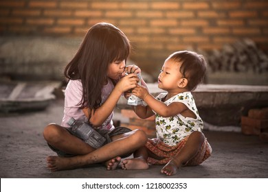 BANGKOK, THAILAND – OCTOBER 28: The little sister is scrambling to milk her sister, who is eating the life of a difficult child because parents have to work on October 28, 2018 in Bangkok, Thailand.