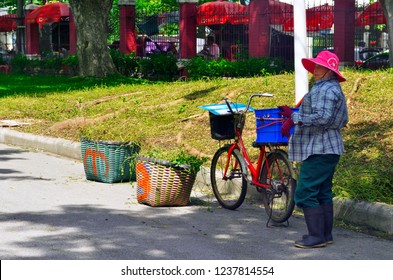 Bangkok, Thailand - October 29, 2014: Woman with a bicycle and wicker baskets full of cut grass in Lumpini Park.
