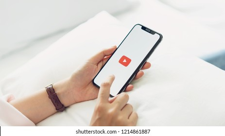 Bangkok, Thailand - October 29, 2018 : hand is pressing the screen displays the Youtube app icons on Apple iPhone. YouTube is the popular online video-sharing website.