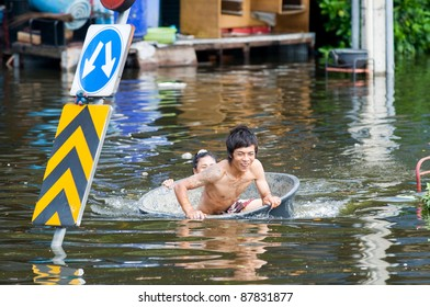 BANGKOK, THAILAND - OCTOBER 29: Man being transported in a tub during the worst flooding in decades in Bangkok, Thailand on October 29, 2011.