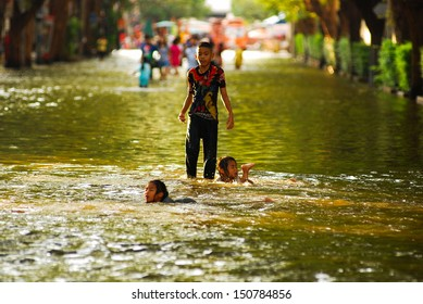 BANGKOK, THAILAND - OCTOBER 30, 2011:Unidentified boy and girl aged 13-15 years enjoy playing in flood water on October 30,2011 Bangkok, Thailand.
