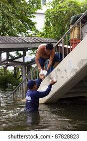 BANGKOK, THAILAND - OCTOBER 30 : The Royal Thai Navy bringing food for people during the monsoon season on October 30,2011  Bangkok, Thailand. A man living on the bridge