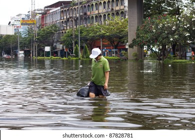 BANGKOK, THAILAND - OCTOBER 30 :  An unidentified woman wading through the flood after the monsoon rain on October 30,2011  Bangkok, Thailand.