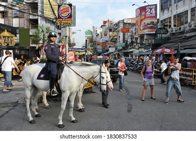 Bangkok, Thailand - October 31, 2012: Tourists walk along backpacker haven Khao San Road as police on horseback patrol the area. Budget accommodation on Khao San Road starts from $6 or B200 per night.