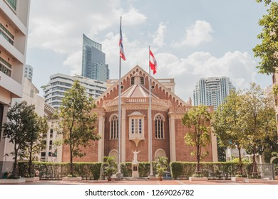 Bangkok, Thailand - October 31, 2015: Assumption Cathedral photographed from Assumption College with Thai flag and Assumption College flag with skyscraper in the background