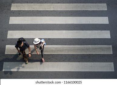 Bangkok Thailand - October 6, 2017: Man and women walking across the crosswalk at the junction street of city, Pedestrian safety, Aerial view