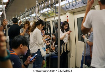 Bangkok Thailand - October 6, 2017: The passengers waiting and using smartphones to kill time inside MRT subway train, Mobile phone addiction lifestyle daily, Social technology telecommunication