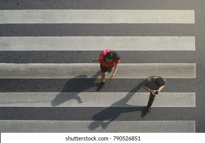 Bangkok Thailand - October 6, 2017: Man and women walking across the crosswalk at the junction street of city, Pedestrian safety, Top view