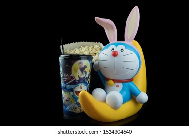 Bangkok, Thailand - October 6, 2019 : Cute toy of Doraemon sit on the half moon. Set of bucket popcorn and soft drink to promote the movie (Doraemon: Nobita's Chronicle of the Moon Exploration)