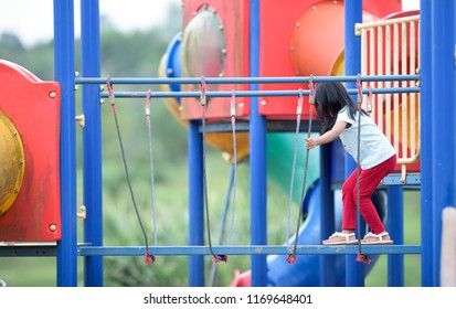BANGKOK, THAILAND - OGOS 1, 2018: Two Caucasian little kids with blond hair play in an outdoor playground consisting of colorful equipment and green trees in the background on a sunny day.