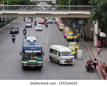 BANGKOK, THAILAND on 7/6/2018: urban city public transporter bus and motorcycle waiting for passenger around a bus stop, authentic shot shows common daily life in the busy hours of the capital city