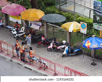 BANGKOK, THAILAND on 7/6/2018: urban city motorcycle taxies waiting around bus and BTS skytrain station, authentic shot shows common daily life in the business busy hours of the THAI capital city