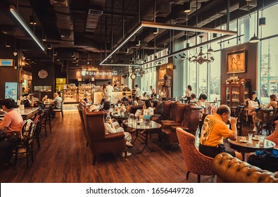 BANGKOK, THAILAND: People drinking coffee and relaxing in cute cafe with modern interior and big windows on January 26, 2020. More than 12,000,000 foreign tourists visit Bangkok every year