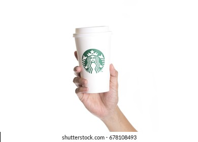 Bangkok, Thailand - Sep 20, 2015: Female hands holding a cup of Starbuck coffee on white background