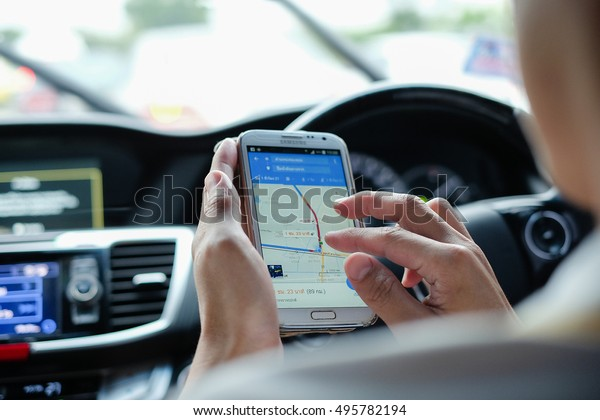 BANGKOK, THAILAND - SEP 23, 2016: Man in the car using a Google Maps on Samsung Note 2. Google Maps is a most popular web mapping service for mobile provided by Google inc.(shallow depth of field)