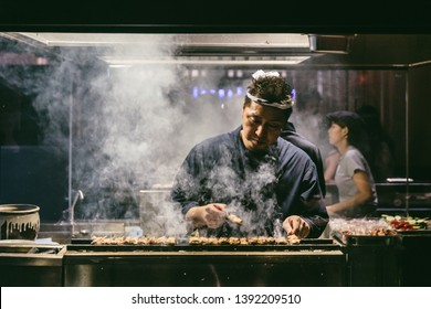 BANGKOK, THAILAND. SEP 28, 2016: Japanese Yakitori Chef is grilling chicken marinated with ginger, garlic and soy sauce with a lot of smoke.