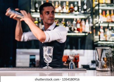BANGKOK, THAILAND. SEP 5, 2016: Male mixologist is making red cocktail by shaking cocktail with shaker on counter bar in the restaurant.